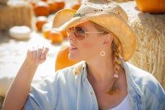 相当白肤金发的女性在南瓜帕特的蓄牧者佩带的牛仔帽 库存图片
