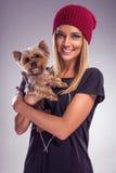 相当白肤金发的妇女在与约克夏狗狗的秋天穿戴了 免版税图库摄影