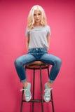 相当白肤金发的妇女坐椅子 免版税库存照片
