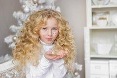 相当白肤金发的小女孩画象吹在五彩纸屑在手在圣诞节演播室 库存图片