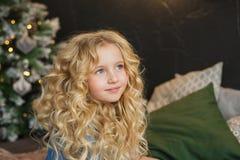 相当白肤金发的小女孩画象微笑并且看起来旁边在圣诞节时间的一张床上 库存图片