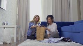 相当白肤金发的展示对她的朋友的一件新的时髦的礼服在家购物以后 影视素材