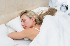相当白肤金发睡觉在与闹钟的床上 库存照片