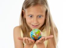 相当看小地球的黄色女衬衫的年轻白肤金发的女孩我 免版税库存照片