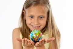 相当看小地球的黄色女衬衫的年轻白肤金发的女孩我 免版税库存图片