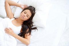 相当睡觉在白色床上的少妇 免版税库存照片