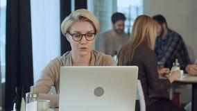 相当研究便携式计算机的愉快的妇女在咖啡馆酒吧的咖啡休息期间 股票录像