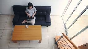 相当研究膝上型计算机的少妇在现代舒适家 股票录像