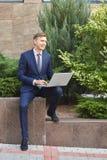 相当研究膝上型计算机的年轻人,当坐户外时 到达天空的企业概念金黄回归键所有权 库存照片