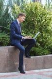 相当研究膝上型计算机的年轻人,当坐户外时 到达天空的企业概念金黄回归键所有权 图库摄影