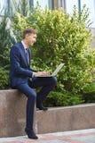 相当研究膝上型计算机的年轻人,当坐户外时 到达天空的企业概念金黄回归键所有权 免版税库存图片