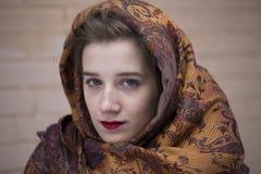相当穿一条五颜六色的围巾的蓝眼睛的女孩 免版税图库摄影