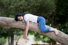 相当穿原因衣裳和拥抱一棵树的可爱的妇女在一个绿色公园 免版税图库摄影