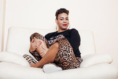 相当穿着体面时髦的非裔美国人的大妈妈的妇女 赃物放松在家,在clothers的豹子印刷品 方式 免版税库存图片