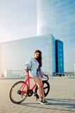 相当站立与她的现代桃红色自行车的年轻棕色毛发的妇女在城市 库存图片