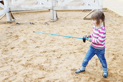 相当站立在与蓝色的沙子的小愉快的女孩 图库摄影