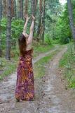 相当站立在森林公路的少妇 库存照片
