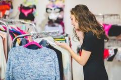 相当端庄的妇女购物在衣裳商店 免版税库存图片