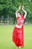 相当红色印度礼服和面纱的亚裔中国肚皮舞表演者 免版税库存图片