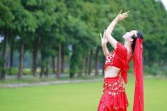 相当红色印度礼服和面纱的亚裔中国肚皮舞表演者 库存图片