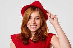 相当红色帽子和T恤杉的时兴的逗人喜爱的年轻欧洲女性游人,愉快探索新的目的地,保留在盖帽的手 免版税库存照片