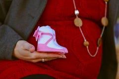 相当红色摆在的孕妇在绿色公园 15个妇女年轻人 免版税库存照片
