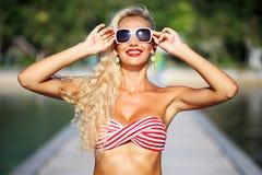 相当红色比基尼泳装的年轻白肤金发的妇女夏天画象  库存照片