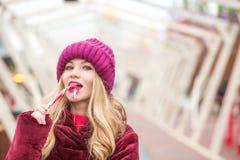 相当红色的白肤金发的女孩编织了摆在与圣诞节cand的帽子 免版税库存图片