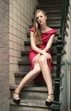 相当红色礼服的白肤金发的妇女 免版税库存照片