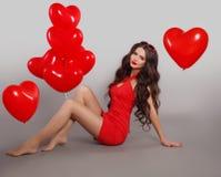 相当红色礼服的逗人喜爱的深色的女孩有心脏形状的迅速增加 免版税库存图片