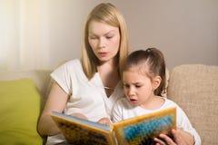 相当美丽的母亲和她的年轻女儿读一本书 图库摄影