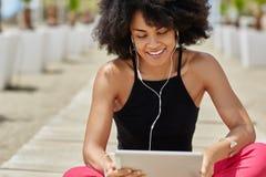 相当美国黑人的在片剂微笑的妇女听的audiobook 免版税库存照片