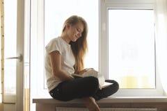 相当翻转通过书的年轻白肤金发的女孩坐窗台 库存图片