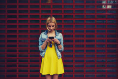 相当聊天在她的智能手机的少妇反对空白的您的内容或正文消息的拷贝空间明亮的背景 免版税库存图片
