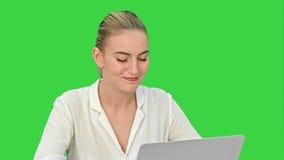 相当肯定地研究在一个绿色屏幕,色度钥匙上的一台膝上型计算机的年轻女商人 影视素材
