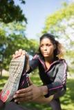 相当舒展她的腿的运动的妇女在公园 库存照片