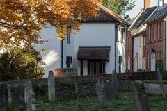 相当英国村庄街道和坟园在秋天 免版税库存照片
