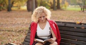 相当读书的少妇在长凳户外在日落 影视素材