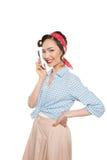 相当谈话在智能手机和微笑对照相机的亚裔画报女孩 库存图片