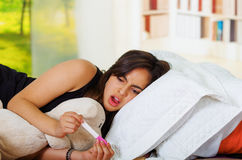 相当躺下年轻深色的妇女,当看怀孕与震惊表情的家测试,书架时 库存图片