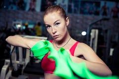 相当运动女孩在健身中心时使用绿色舒展带,当行使 库存照片