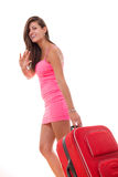 相当运载红色旅行手提箱和微笑的少妇 免版税库存图片