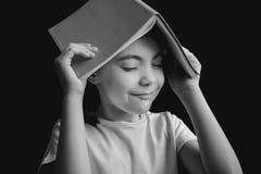 相当逗人喜爱的有习字簿的女孩白色T恤杉以在黑背景的一个屋顶的形式 黑白图象 免版税库存图片
