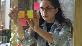 相当采取色的办公室贴纸和小心地投入他们的年轻女性女实业家在glassboard在现代 股票录像