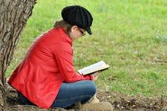 相当青少年女孩阅读书在大结构树下 库存照片