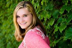 相当青少年的女孩桃红色毛线衣&绿色常春藤 库存图片