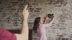 相当,当她的男朋友做框架形状与时,亚裔妇女选择被构筑的照片的地方砖墙的 股票录像