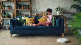 相当,当机器人真空吸尘器清洗做人的时,地毯家事小姐使用智能手机触摸屏 影视素材