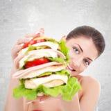 给我们一个巨大的三明治的妇女 免版税库存图片