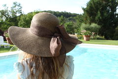 相当戴一个棕色帽子的女孩在水池的边缘 免版税库存照片